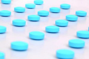 Cluster of blue pills spread out against white background