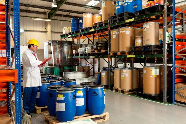 Man in chemicals warehouse with hard hat and clipboard checking stock