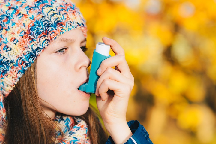 Asthma patient girl using inhaler in park. Asthma concept.