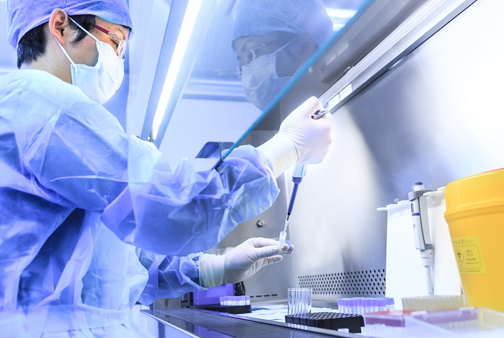 Chinese female scientist in lab with pipette and containers