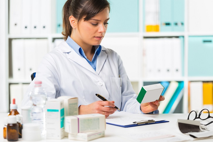 Female pharmacist sat at desk writing notes with medicine boxes in background.