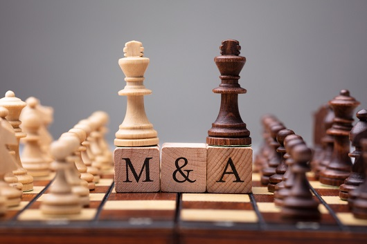 chess pieces mounted on scrabble squares spelling M&A, illustrating mergers and acquisitions concept