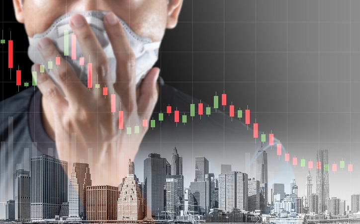 Close up of person wearing mask with city landscape and declining shares chart in background, representing business interruption insurance concerns in the wake of covid-19.