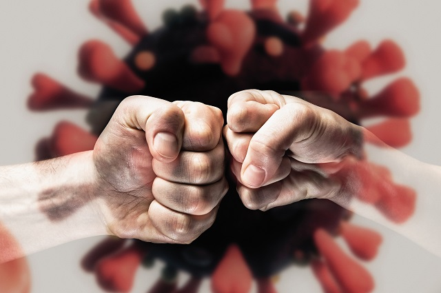 Fists punching each other, with virus in background.